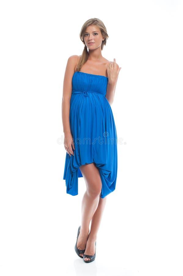 Gravid modemodell i en blå klänning för havandeskap beklär gravid kvinna arkivbilder