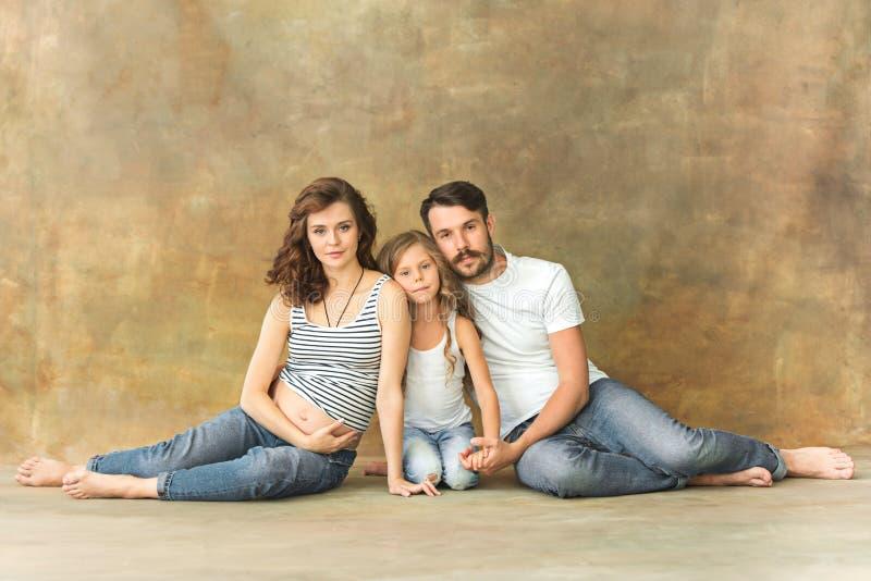 Gravid moder med den tonåriga dottern och maken Familjstudiostående över brun bakgrund royaltyfri bild