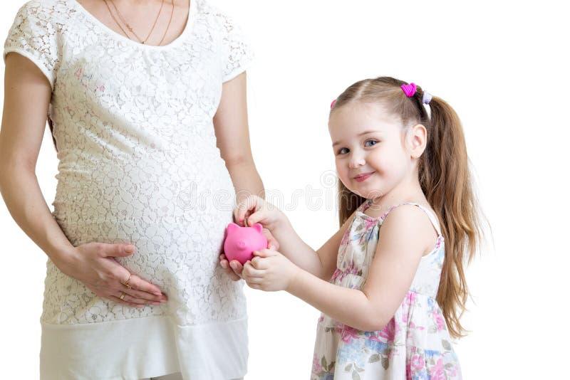 Gravid moder och barn som sätter mynt in i piggy fotografering för bildbyråer