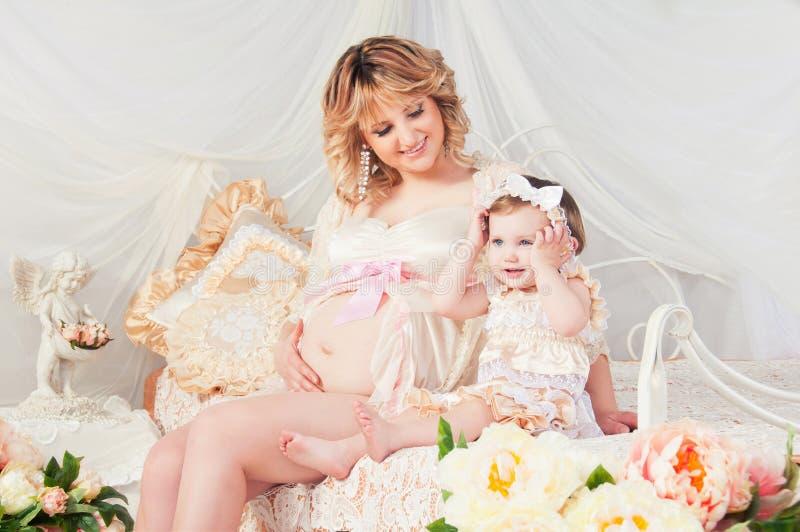 Gravid moder och gullig liten dotter i hemtrevligt rum med blommor arkivfoton