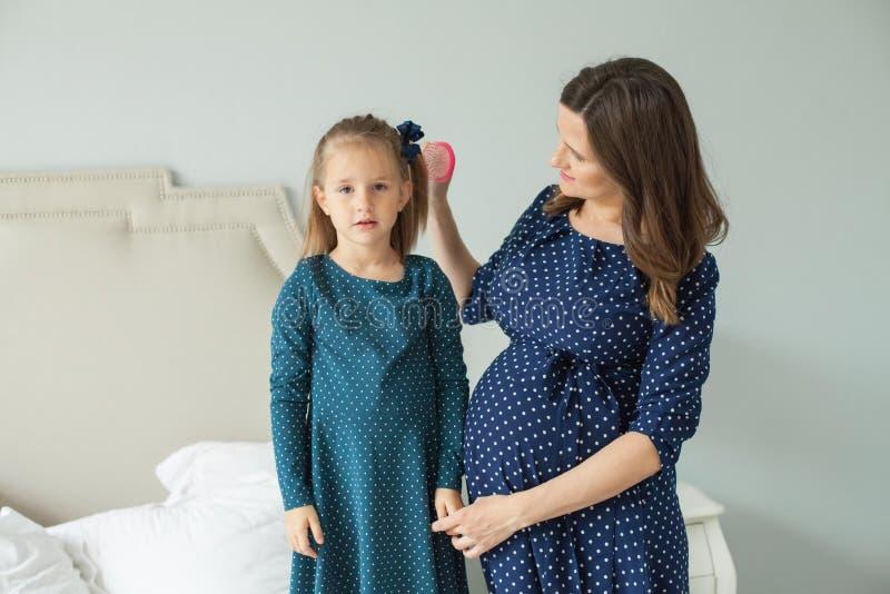 Gravid moder och liten dotter Moder som kammar barnflickan arkivfoton