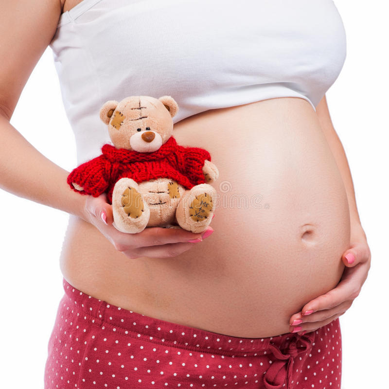 Gravid moder som visar hennes buk och innehav en nalle arkivbilder
