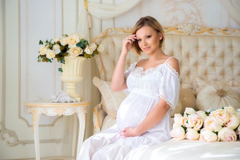 Gravid modersammanträde på en säng av rosor royaltyfria foton