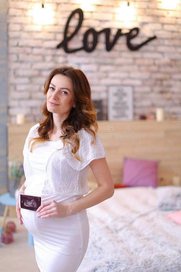 Gravid nätt kvinna som håller ultraljudfotoet och bär den vita klänningen, inskriftförälskelse på tegelstenväggen royaltyfria bilder