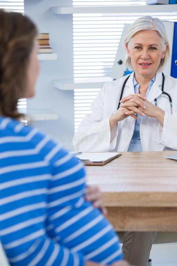 Gravid patient som konsulterar en doktor arkivbild