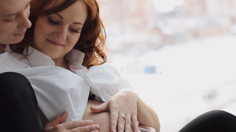 Gravid sammanträde för ung kvinna nära fönstret Försiktigt pressande till en lycklig make långsam rörelse