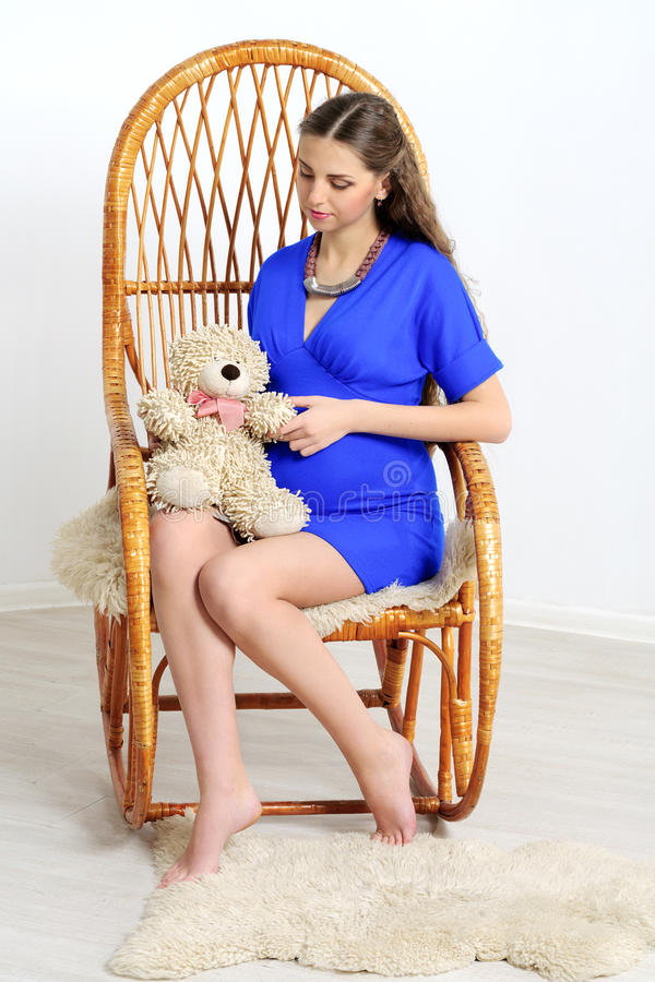 Gravid sammanträde i stol och innehav en leksak royaltyfria bilder