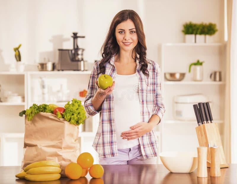 Gravid ung kvinna i kök med packen royaltyfria bilder