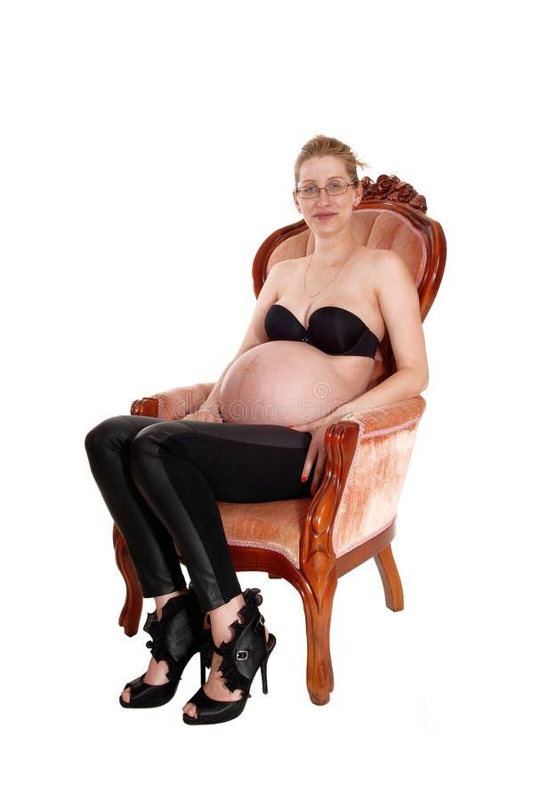 Gravid vit kvinna i fåtölj arkivbild