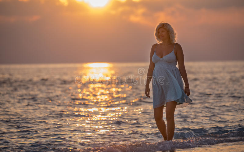 Gravida kvinnan går på den maldiviska stranden under soluppgången arkivfoto