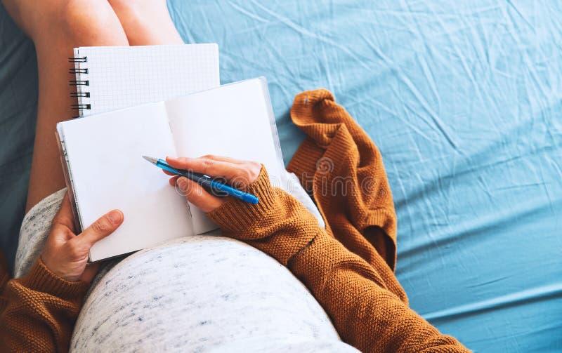 Gravida kvinnan gör anmärkningar och att se medicinska dokument royaltyfri bild