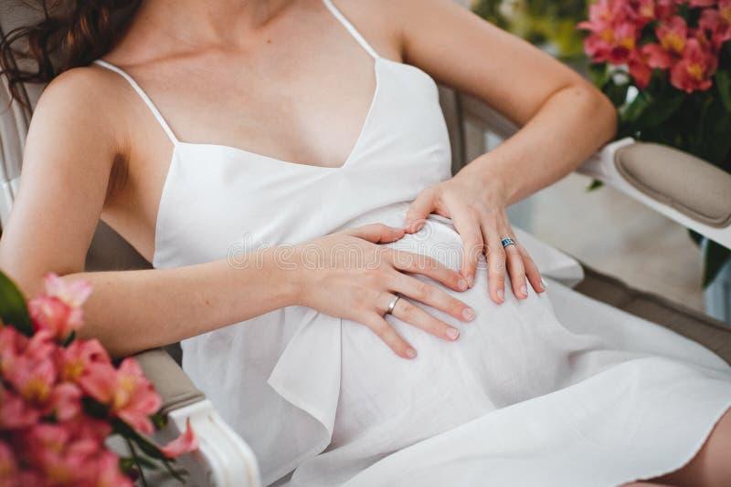 Gravida kvinnan i den vita klänningen sitter på en stol utomhus och hållhänder på buken Havandeskap, föräldraskap, förberedelse o arkivfoton