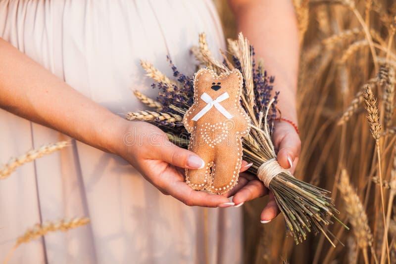 Gravida kvinnan i liliacklänning rymmer en bukett av lavendel och vete och en nallebjörn arkivfoton