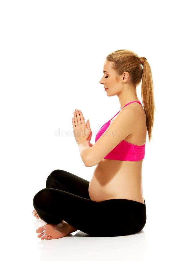 Gravida kvinnan kopplar av att göra yoga arkivfoton