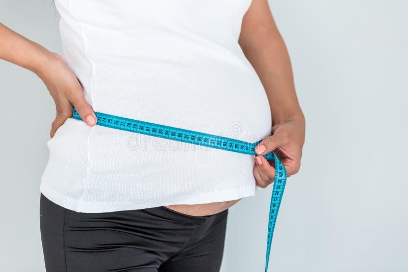 Gravida kvinnan mäter hennes mage vid måttbandet - som isoleras på blekt - blå bakgrund arkivfoto