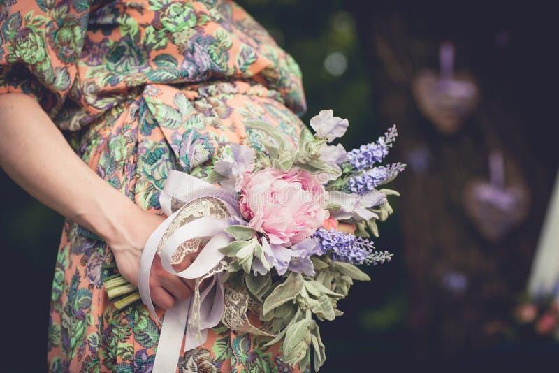 Gravida kvinnan med den ljusa sommarbuketten av blommor rymmer händer på buken på en solig dag utomhus Havandeskap föräldraskap,  royaltyfria foton