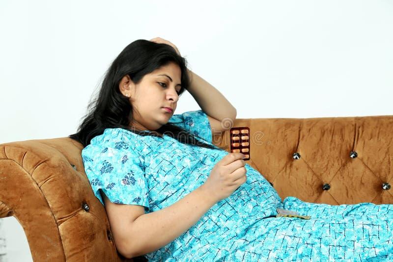 Gravida kvinnan rymmer medicin i hand med att se royaltyfria foton