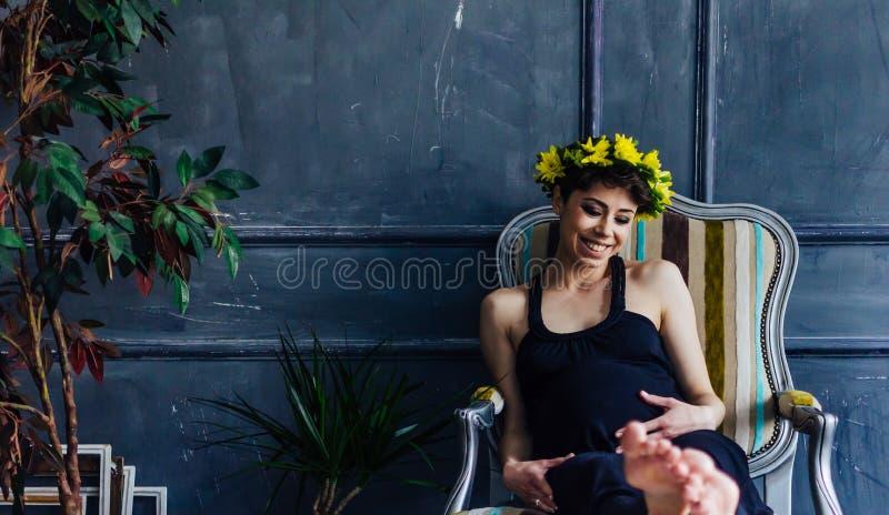 Gravida kvinnan sitter i en fåtölj vid fönstret bredvid träd Hon ser hänsynsfullt på hennes buk royaltyfri fotografi