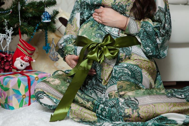 Gravida kvinnan sitter nära julgranen hemma arkivbilder