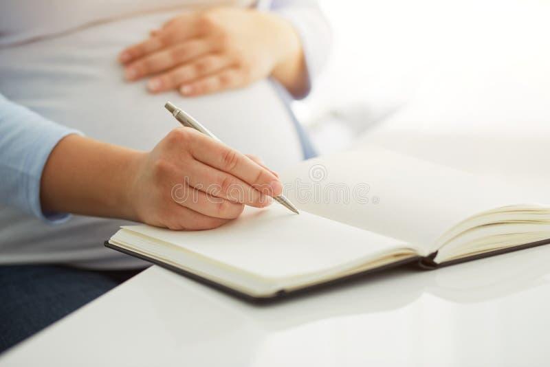 Gravida kvinnan skriver till hennes dagbok royaltyfri fotografi