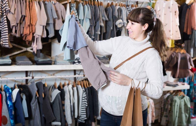 Gravida kvinnan som avgör på kläder för, behandla som ett barn i children'skoagulering royaltyfri foto