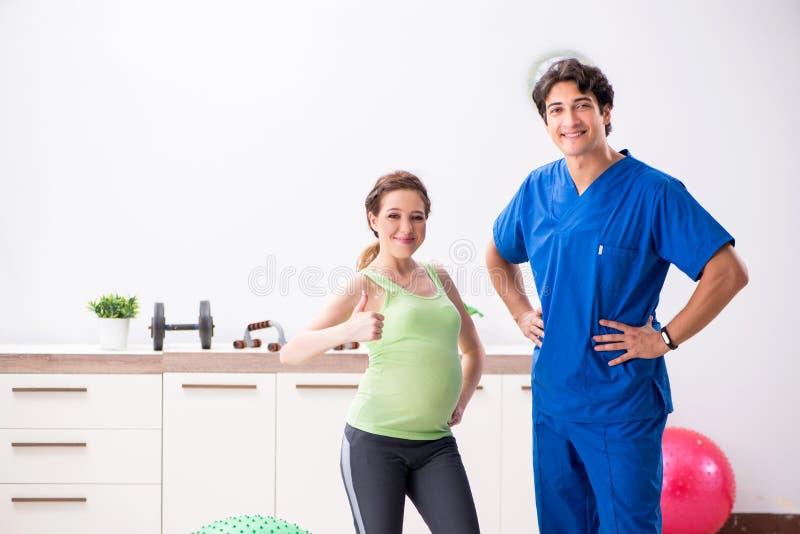 Gravida kvinnan som gör fysiska exercies med instruktören arkivfoto