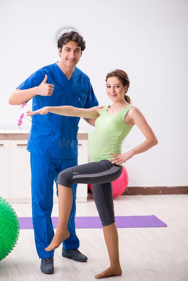 Gravida kvinnan som gör fysiska exercies med instruktören royaltyfri foto