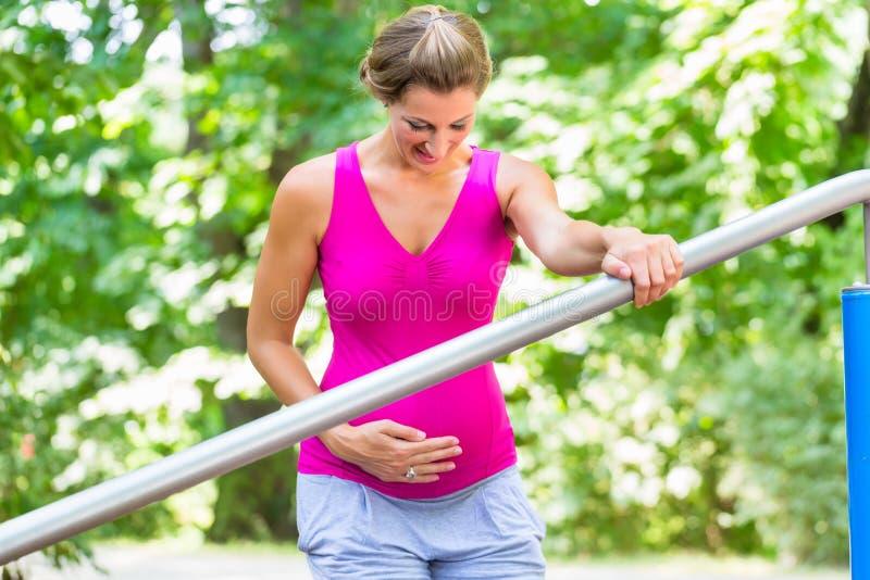 Gravida kvinnan som gör havandeskap, övar på Kondition-slinga royaltyfria foton