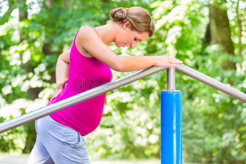 Gravida kvinnan som gör havandeskap, övar på Kondition-slinga arkivbild