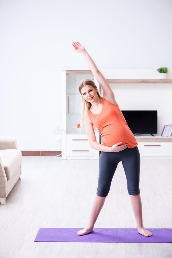 Gravida kvinnan som hemma gör sportövning fotografering för bildbyråer