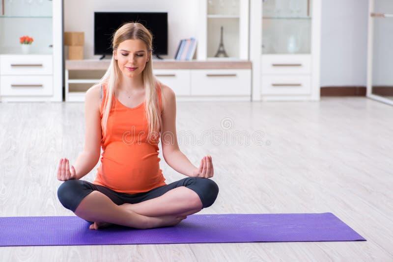 Gravida kvinnan som hemma gör sportövning arkivfoton