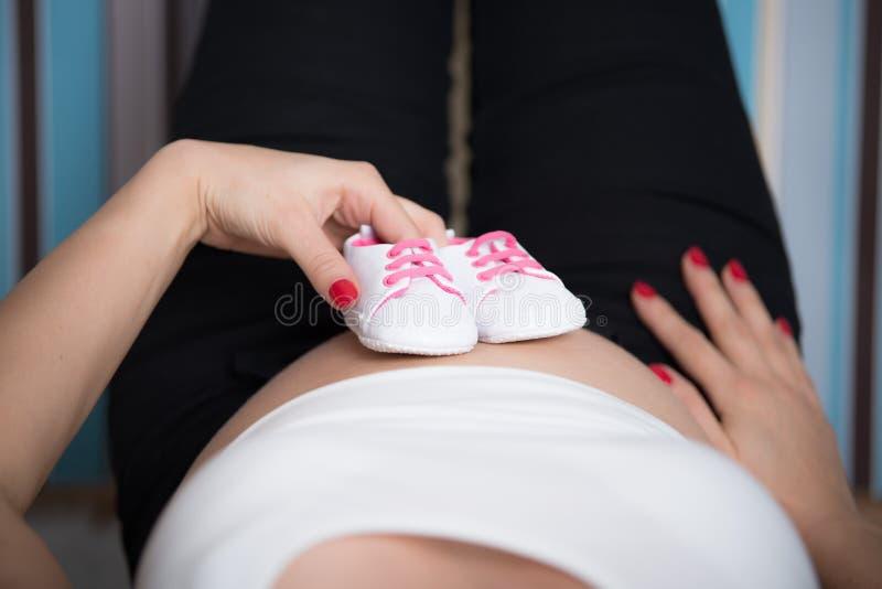 Gravida kvinnan som rymmer ett mycket litet, behandla som ett barn skor på hennes buk arkivbilder