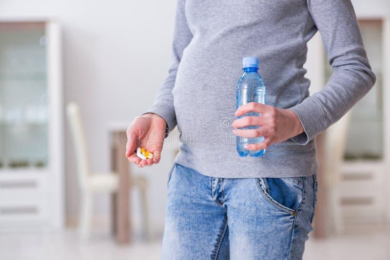 Gravida kvinnan som tar preventivpillerar under havandeskap royaltyfri fotografi