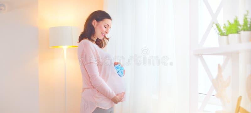 Gravida kvinnan som trycker på hennes buk och spelar med lite, behandla som ett barn skor Lycklig gravid mitt åldras moder hemma royaltyfria bilder