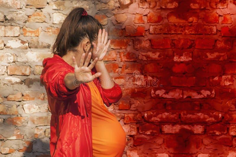 Gravida kvinnor är rädda Hon tog upp sina händer som ett tecken på skydd mot rädsla och negativa känslor Hon döljer sitt ansikte fotografering för bildbyråer