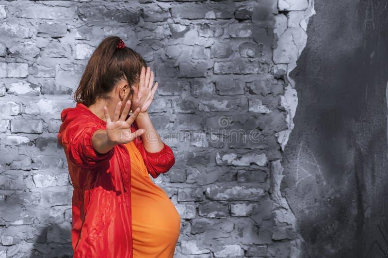 Gravida kvinnor är rädda Hon tog upp sina händer som ett tecken på skydd mot rädsla och negativa känslor Hon döljer sitt ansikte royaltyfri bild