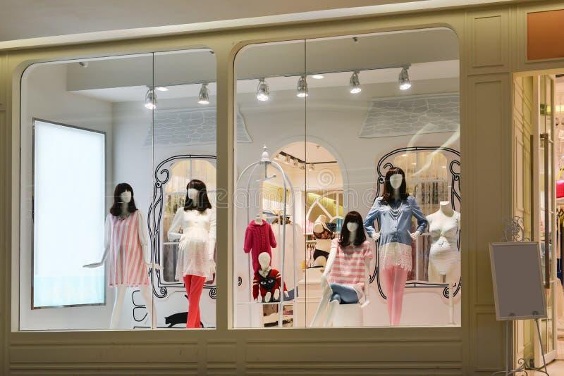 Gravida kvinnor och barnskyltdockor i mode shoppar fönstret royaltyfri foto