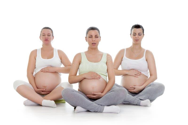 Gravida kvinnor som gör andningövning royaltyfri fotografi
