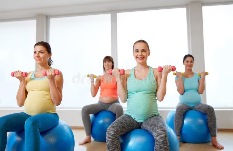 Gravida kvinnor som utbildar med övningsbollar i idrottshall royaltyfri bild