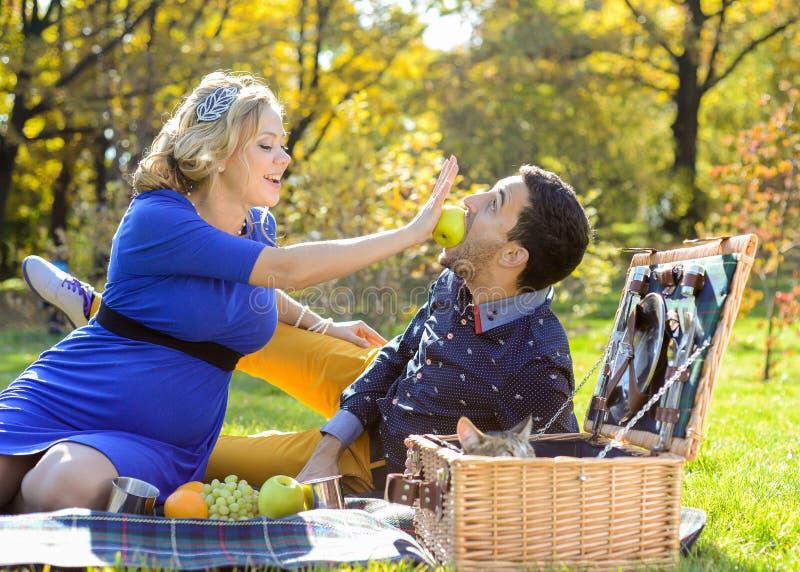 Gravida lyckliga och le par på picknick med katten arkivfoto