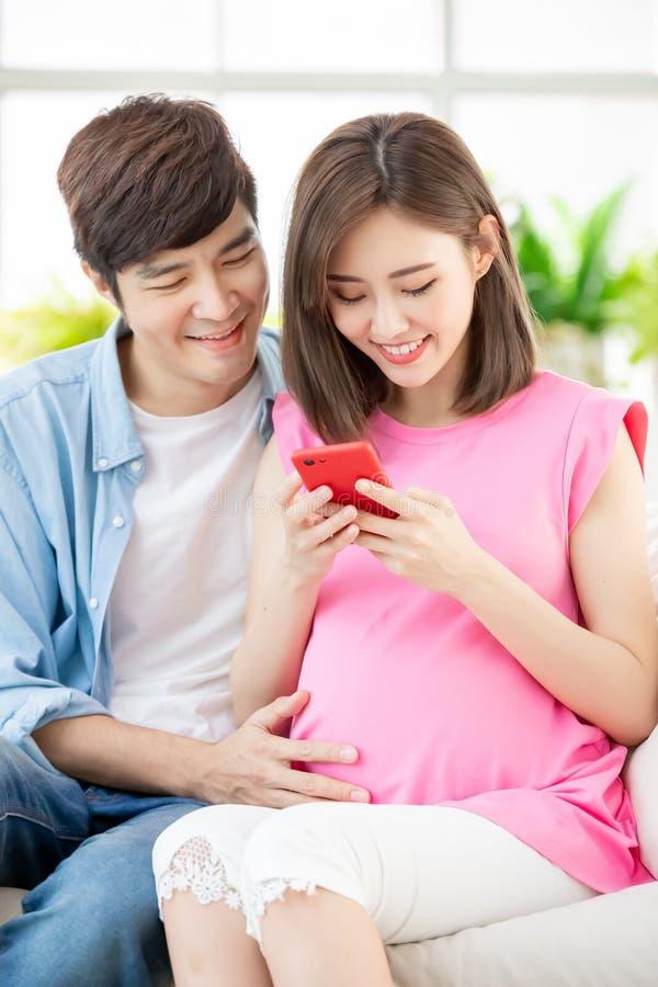 Gravida par använder den smarta telefonen arkivbild