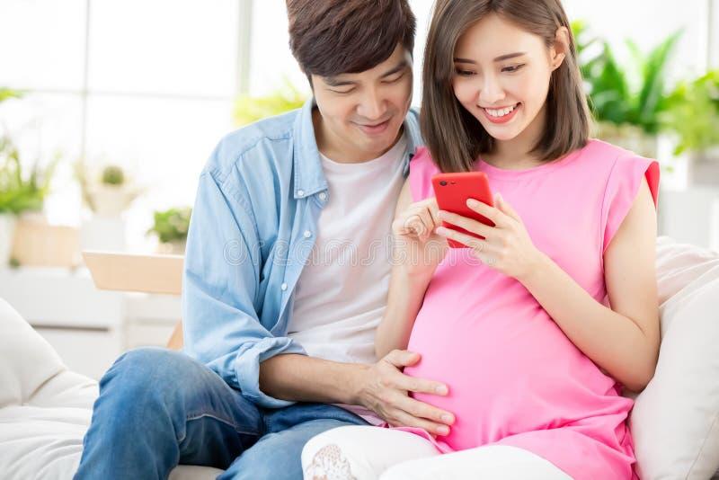 Gravida par använder den smarta telefonen fotografering för bildbyråer