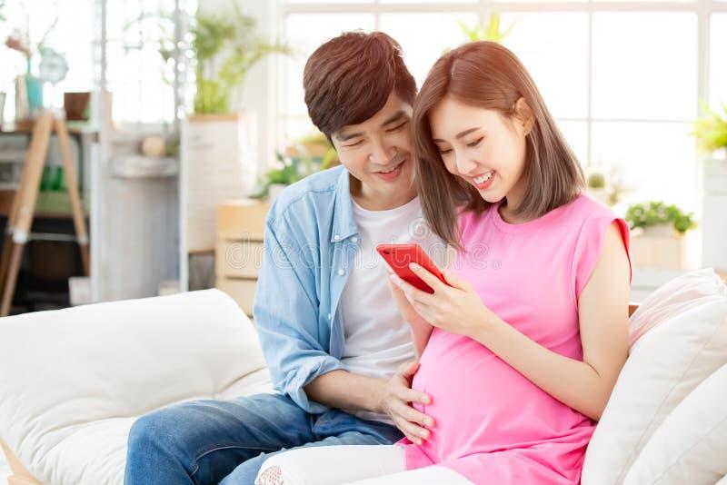 Gravida par använder den smarta telefonen royaltyfri fotografi