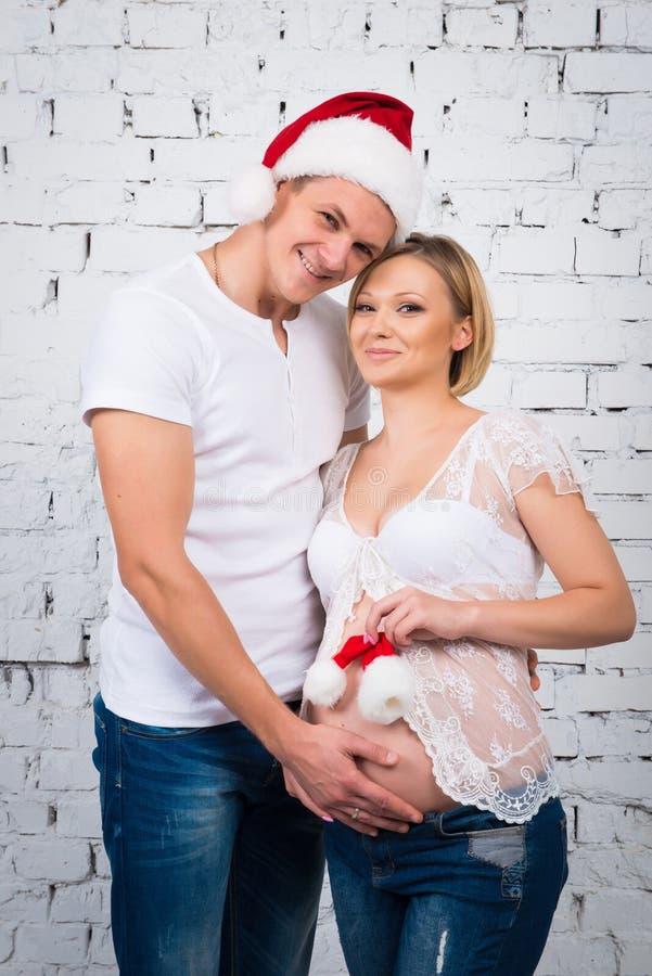 Gravida par för barn nära en vit tegelstenvägg med en småbarnjultomtenhatt royaltyfria foton