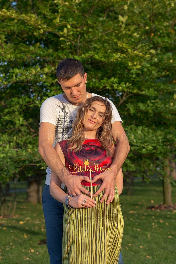 Gravida par för barn - utomhus- kramar arkivbilder
