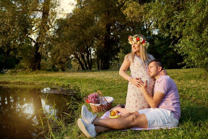 Gravida par i parkera vid sjön i strålarna av solljus royaltyfria bilder