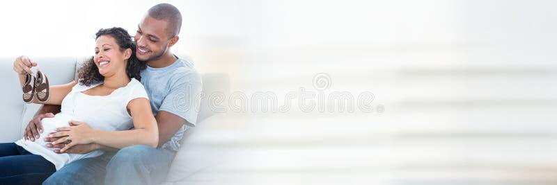Gravida par med behandla som ett barn skor och oskarp vit övergång arkivbilder