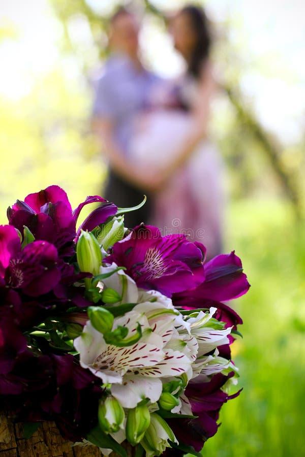 Gravida par och bukett av blommor i förgrunden royaltyfria bilder