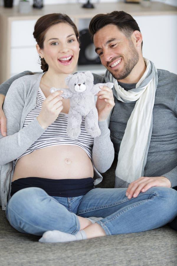 Gravida par som rymmer den mjuka nallebjörnen arkivfoton