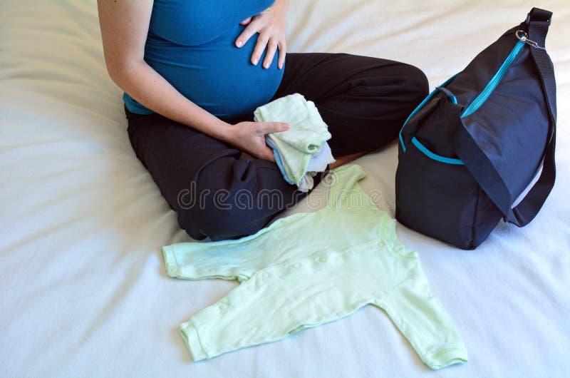Gravidanza - donna incinta che imballa una borsa dell'ospedale fotografie stock